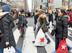 買い物袋を手に街を歩く人たち(12月22日、ニューヨーク)