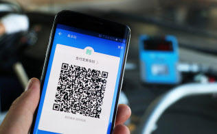 A passenger uses his smartphone to scan a QR code of the electronic bus card to pay for bus fees in a bus in Nanjing city, east China's Jiangsu province, 1 September 2017.