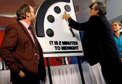 「世界終末時計」を30秒進め、残り2分に設定する米科学誌の担当者(25日、ワシントン)=ロイター