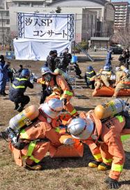 コンサート会場を想定した爆発テロの対処訓練で、けが人を運び出す消防隊員ら(29日午前、東京都荒川区の都立汐入公園)=共同