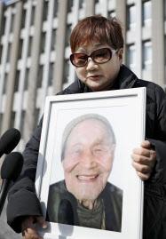 判決後、大久保文雄さんの遺影を手に質問に答える原告で次男の妻の美江子さん(20日午後、福島地裁前)=共同
