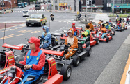 公道を列をなして走るたくさんのカート=東京都港区(人物の顔を画像加工しています)=共同