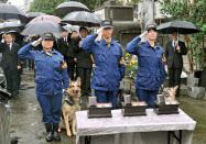 警察犬の慰霊祭で慰霊碑に向かい敬礼する警視庁鑑識課の担当者ら(21日、東京都板橋区)=共同