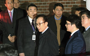 収賄や横領などの容疑で移送される李明博元大統領(23日、ソウル)=AP