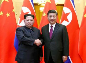 北京の人民大会堂で握手する北朝鮮の金正恩朝鮮労働党委員長(左)と中国の習近平国家主席=新華社・共同