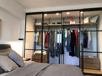 寝室とクローゼットを仕切る壁をガラスにして、服や帽子などをあえて見せて収納した