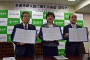 調印を終え協定書を見せる郡和子・仙台市長(中央)ら