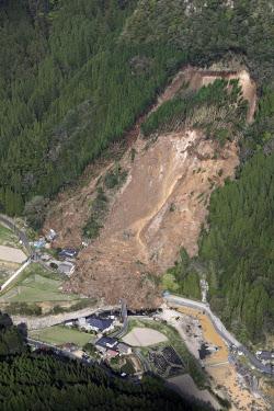 大分県中津市耶馬渓町で山が崩落し、民家が巻き込まれた現場(11日午前)=共同
