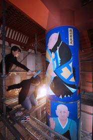 再建中の興福寺の中金堂で、法相柱に仕上げの筆を入れる畠中光享さん(右)(16日午前、奈良市)