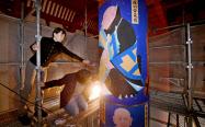 再建中の興福寺の中金堂で、法相柱に仕上げの筆を入れる畠中光享さん(右)(16日午前、奈良市)=山本博文撮影