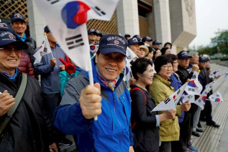 南北首脳会談のため青瓦台を出発する文大統領の車列を待ちながら国旗を持つ支持者ら(27日、ソウル)=ロイター