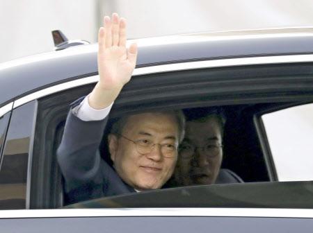 沿道に集まった人たちに手を振り、南北首脳会談が行われる板門店に向かう文大統領(27日、ソウル)=共同