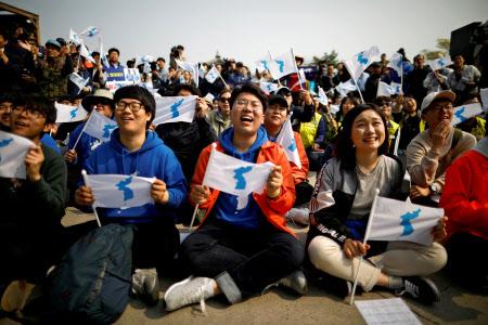 統一旗を手に首脳会談の中継を見る人たち(27日、韓国・パジュ市)=ロイター