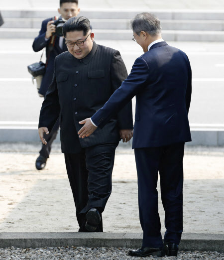 軍事境界線を超えて韓国側に入る金委員長(左)=代表撮影・AP