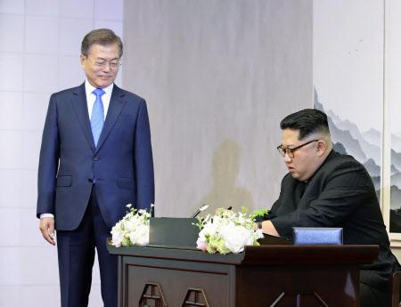 9時42分ごろ 芳名録にサインする北朝鮮の金委員長(右)=代表撮影・AP
