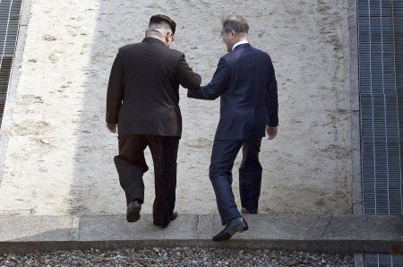 手をつなぎ北朝鮮側に入る文大統領(右)と金委員長=代表撮影・AP