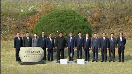 16時40分ごろ、記念植樹後に記念撮影する韓国の文大統領(中央)と北朝鮮の金委員長(左から6人目)=代表撮影・ロイター
