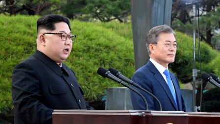 共同宣言について会見する金委員長(左)と文大統領=ロイター