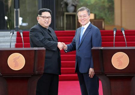 共同宣言の会見を終え、握手する文大統領(右)と金委員長=AP