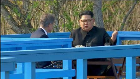散歩の途中、ベンチに腰掛けて話を始めた金正恩氏(右)と文在寅氏=ロイター