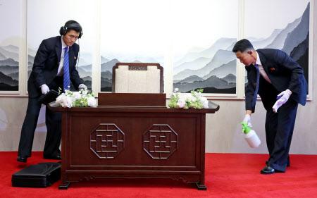 金正恩委員長が芳名録にサインする前、机のチェックや消毒をする北朝鮮側の要員=ロイター