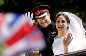 19日、ロンドン郊外ウィンザーで結婚式後のパレードで手を振るヘンリー英王子(左)とメーガン妃=ロイター
