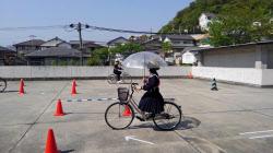 傘を差して自転車に乗ると危ないことを体験する高校1年生ら(4月、兵庫県姫路市の姫路高校)