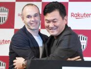 楽天の三木谷会長(右)と抱き合うサッカースペイン代表のイニエスタ選手(24日、東京都港区)