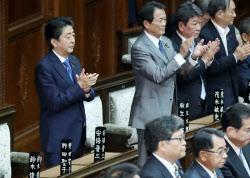 働き方改革関連法案が衆院本会議で可決され、自席で拍手する安倍首相(左、31日午後)
