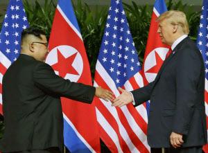 会談の冒頭で握手を交わす北朝鮮の金正恩委員長(左)とトランプ米大統領(12日、シンガポール)=AP