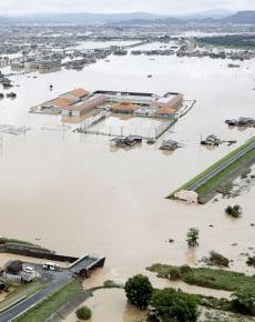 冠水した岡山県倉敷市の真備町地区。手前は決壊した堤防