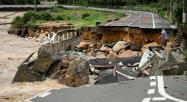 濁流に削られて崩壊した道路。東広島市(手前)から広島市安佐北区へと続いていた(7日) 〔時事〕
