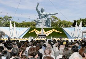 平和祈念式典で放たれたハトと平和祈念像(9日午前、長崎市の平和公園)