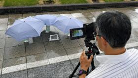 暑さ対策の実証実験として、散水した歩道に日傘を差した場合の路面温度を測定した(13日、東京都千代田区)=共同