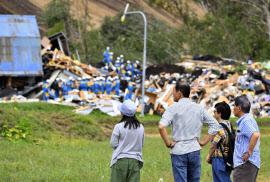 土砂崩れ現場で行われた行方不明者の捜索を見つめる人たち(7日、北海道厚真町吉野地区)=共同