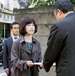東京医科大の担当者(右)に通知書を渡す弁護団共同代表の打越さく良弁護士(29日午後、東京都新宿区)=共同