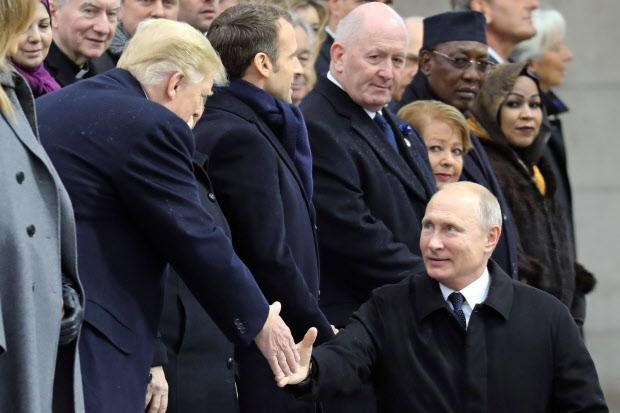 トランプ米大統領(左)と握手するロシアのプーチン大統領=ロイター