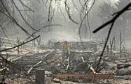 米カリフォルニア州の火災現場で捜索する消防士(16日)=AP