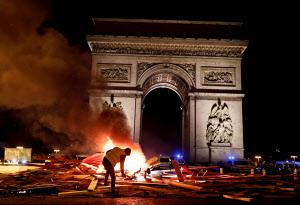 24日、パリのシャンゼリゼ大通りで、シンボルの「黄色いベスト」を着けたデモ隊ら数千人と治安部隊が大規模衝突を展開した=ロイター