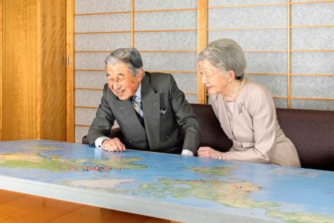 世界地図を眺めながら過去の外国訪問を振り返る天皇、皇后両陛下(10日、皇居・御所の応接室)=宮内庁提供