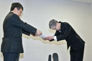 国交省の蝦名邦晴航空局長(左)から業務改善勧告の文書を受け取る日本航空の赤坂祐二社長(11日午前、国交省)