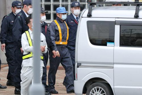 作業着のような服装で軽自動車に乗り込むゴーン元会長(右から2人目)=6日午後、東京都葛飾区の東京拘置所