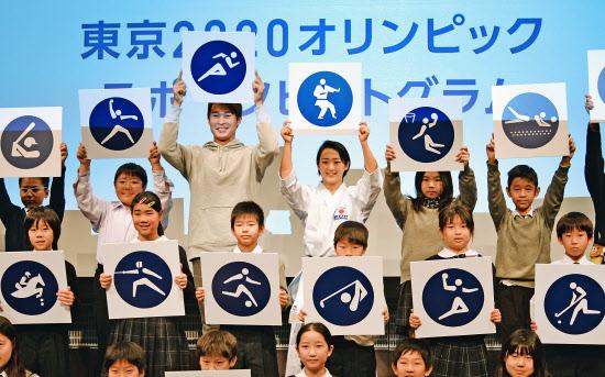 2020年東京五輪のスポーツピクトグラムを発表する陸上の飯塚選手(後列左から3人目)と空手の清水選手(同4人目)ら=12日午前、東京都江東区(森山有紗撮影)