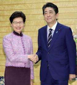 会談を前に香港の林鄭行政長官(左)と握手する安倍首相(9日午前、首相官邸)