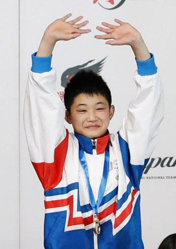 飛び込みの日本室内選手権の男子高飛び込みで優勝し、表彰式で声援に応える玉井陸斗。12歳での優勝は史上最年少(21日、東京辰巳国際水泳場)=共同